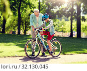 Купить «grandfather and boy with bicycle at summer park», фото № 32130045, снято 9 июля 2016 г. (c) Syda Productions / Фотобанк Лори