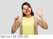 Купить «happy asian woman with red clown nose», фото № 32130121, снято 11 мая 2019 г. (c) Syda Productions / Фотобанк Лори