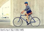 Купить «young hipster man with bag riding fixed gear bike», фото № 32130145, снято 15 июня 2016 г. (c) Syda Productions / Фотобанк Лори
