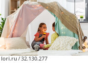 Купить «girls playing with torch in kids tent at home», фото № 32130277, снято 18 февраля 2018 г. (c) Syda Productions / Фотобанк Лори
