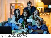 Купить «friends taking picture by selfie stick at home», фото № 32130765, снято 22 декабря 2018 г. (c) Syda Productions / Фотобанк Лори