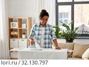 Купить «african american woman ironing bed linen at home», фото № 32130797, снято 7 апреля 2019 г. (c) Syda Productions / Фотобанк Лори