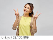 Купить «happy asian woman showing peace», фото № 32130809, снято 11 мая 2019 г. (c) Syda Productions / Фотобанк Лори