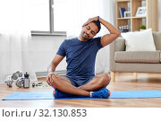 man training and stretching body at home. Стоковое фото, фотограф Syda Productions / Фотобанк Лори