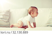 little baby in diaper crawling along sofa at home. Стоковое фото, фотограф Syda Productions / Фотобанк Лори