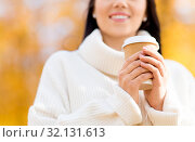 Купить «happy young woman drinking coffee in autumn park», фото № 32131613, снято 13 октября 2018 г. (c) Syda Productions / Фотобанк Лори