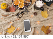 Купить «smartphone, hot chocolate and autumn leaves», фото № 32131897, снято 26 октября 2018 г. (c) Syda Productions / Фотобанк Лори
