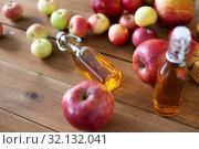 Купить «bottles of apple juice or vinegar on wooden table», фото № 32132041, снято 23 августа 2018 г. (c) Syda Productions / Фотобанк Лори