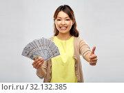Купить «asian woman with dollar money showing thumbs», фото № 32132385, снято 11 мая 2019 г. (c) Syda Productions / Фотобанк Лори