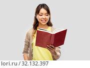 Купить «happy asian woman reading book», фото № 32132397, снято 11 мая 2019 г. (c) Syda Productions / Фотобанк Лори
