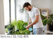 Купить «man spraying houseplants with water at home», фото № 32132405, снято 22 мая 2019 г. (c) Syda Productions / Фотобанк Лори