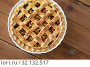 Купить «close up of apple pie in mold on wooden table», фото № 32132517, снято 23 августа 2018 г. (c) Syda Productions / Фотобанк Лори