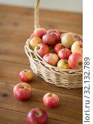 Купить «ripe apples in wicker basket on wooden table», фото № 32132789, снято 24 августа 2018 г. (c) Syda Productions / Фотобанк Лори