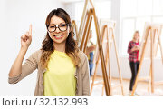 Купить «asian woman in glasses or student with finger up», фото № 32132993, снято 11 мая 2019 г. (c) Syda Productions / Фотобанк Лори