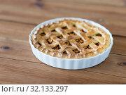 Купить «apple pie in baking mold on wooden table», фото № 32133297, снято 23 августа 2018 г. (c) Syda Productions / Фотобанк Лори