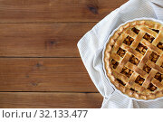 Купить «close up of apple pie in mold on wooden table», фото № 32133477, снято 23 августа 2018 г. (c) Syda Productions / Фотобанк Лори