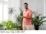 Купить «indian man taking care of houseplants at home», фото № 32134197, снято 19 мая 2019 г. (c) Syda Productions / Фотобанк Лори
