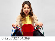 Купить «happy asian woman with open shopping bags», фото № 32134369, снято 11 мая 2019 г. (c) Syda Productions / Фотобанк Лори