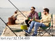 Купить «happy friends fishing and drinking beer on pier», фото № 32134489, снято 8 сентября 2018 г. (c) Syda Productions / Фотобанк Лори