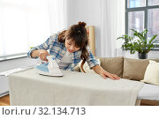 Купить «asian woman or housewife ironing bed linen at home», фото № 32134713, снято 13 апреля 2019 г. (c) Syda Productions / Фотобанк Лори