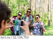 friends with backpacks being photographed on hike. Стоковое фото, фотограф Syda Productions / Фотобанк Лори