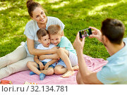Купить «father taking picture of family on picnic at park», фото № 32134781, снято 30 июня 2019 г. (c) Syda Productions / Фотобанк Лори