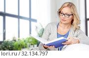 Купить «woman reading book and sitting on couch», фото № 32134797, снято 27 ноября 2015 г. (c) Syda Productions / Фотобанк Лори