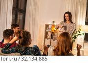 Купить «happy friends playing charades at home in evening», фото № 32134885, снято 22 декабря 2018 г. (c) Syda Productions / Фотобанк Лори