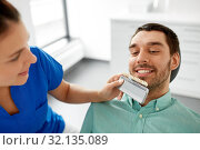 Купить «dentist choosing tooth color for patient at clinic», фото № 32135089, снято 22 апреля 2018 г. (c) Syda Productions / Фотобанк Лори