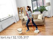 Купить «asian woman or housewife with mop singing at home», фото № 32135317, снято 13 апреля 2019 г. (c) Syda Productions / Фотобанк Лори
