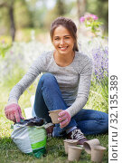 Купить «woman filling pots with soil at summer garden», фото № 32135389, снято 12 июля 2019 г. (c) Syda Productions / Фотобанк Лори