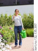 Купить «young woman watering flowers at garden», фото № 32135397, снято 12 июля 2019 г. (c) Syda Productions / Фотобанк Лори