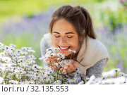 Купить «close up of woman smelling chamomile flowers», фото № 32135553, снято 12 июля 2019 г. (c) Syda Productions / Фотобанк Лори