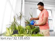 Купить «indian man watering houseplants at home», фото № 32135653, снято 19 мая 2019 г. (c) Syda Productions / Фотобанк Лори