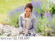 Купить «young woman with flowers at summer garden», фото № 32135697, снято 12 июля 2019 г. (c) Syda Productions / Фотобанк Лори