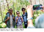 Купить «friends with backpacks being photographed on hike», фото № 32135797, снято 15 июня 2019 г. (c) Syda Productions / Фотобанк Лори