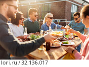 Купить «friends having dinner or bbq party on rooftop», фото № 32136017, снято 2 сентября 2018 г. (c) Syda Productions / Фотобанк Лори