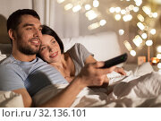 Купить «happy couple watching tv in bed at night at home», фото № 32136101, снято 27 января 2018 г. (c) Syda Productions / Фотобанк Лори