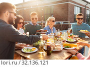 Купить «happy friends eating at barbecue party on rooftop», фото № 32136121, снято 2 сентября 2018 г. (c) Syda Productions / Фотобанк Лори