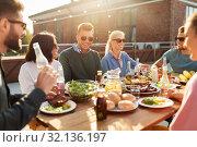 Купить «friends having dinner or bbq party on rooftop», фото № 32136197, снято 2 сентября 2018 г. (c) Syda Productions / Фотобанк Лори