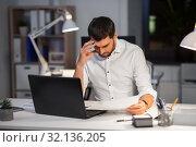 Купить «businessman with papers working at night office», фото № 32136205, снято 25 января 2019 г. (c) Syda Productions / Фотобанк Лори