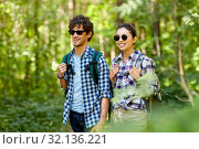 Купить «mixed race couple with backpacks hiking in forest», фото № 32136221, снято 15 июня 2019 г. (c) Syda Productions / Фотобанк Лори