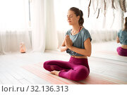 Купить «woman meditating in lotus pose at yoga studio», фото № 32136313, снято 21 июня 2018 г. (c) Syda Productions / Фотобанк Лори