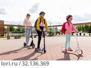 Купить «happy school children with mother riding scooters», фото № 32136369, снято 4 августа 2019 г. (c) Syda Productions / Фотобанк Лори