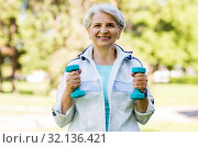 senior woman with dumbbells exercising at park. Стоковое фото, фотограф Syda Productions / Фотобанк Лори