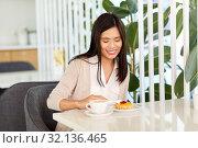 Купить «asian woman eating cake with coffee at cafe», фото № 32136465, снято 13 июля 2019 г. (c) Syda Productions / Фотобанк Лори