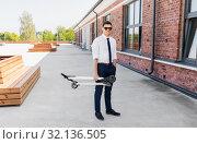 Купить «businessman with folding scooter on rooftop», фото № 32136505, снято 1 августа 2019 г. (c) Syda Productions / Фотобанк Лори