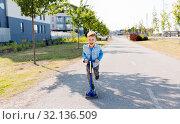 Купить «happy little boy riding scooter in city», фото № 32136509, снято 1 августа 2019 г. (c) Syda Productions / Фотобанк Лори