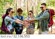 friends with backpacks stacking hands in forest. Стоковое фото, фотограф Syda Productions / Фотобанк Лори