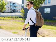 Купить «businessman with backpack riding electric scooter», фото № 32136613, снято 1 августа 2019 г. (c) Syda Productions / Фотобанк Лори